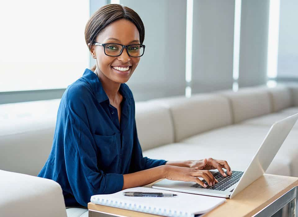 Young woman smiling typing on a laptop