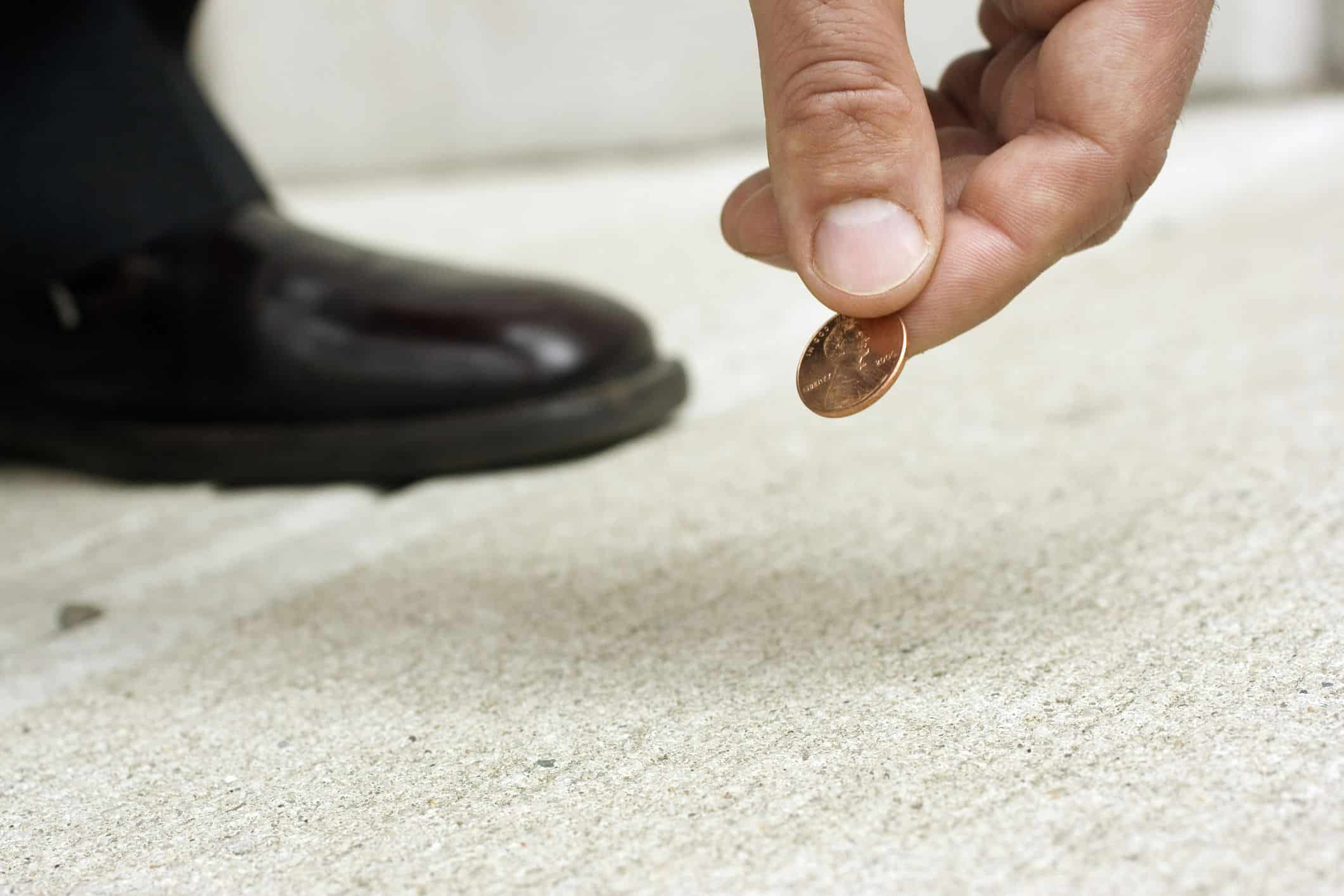 man hand picking up a penny