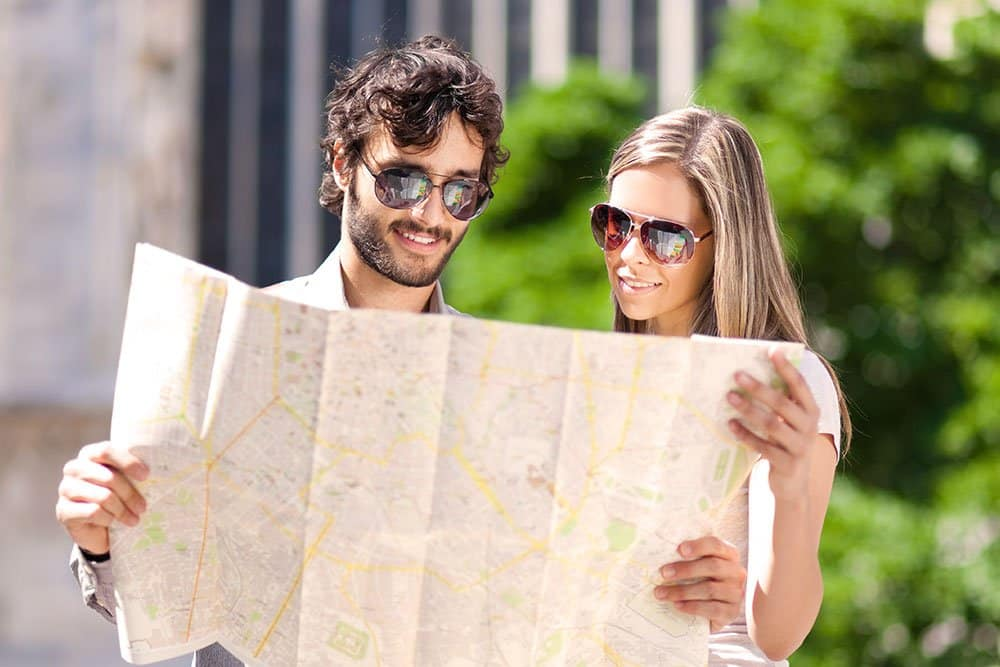 A couple looking at a map smiling while on vacation