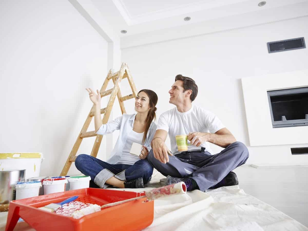 Happy couple painting new house